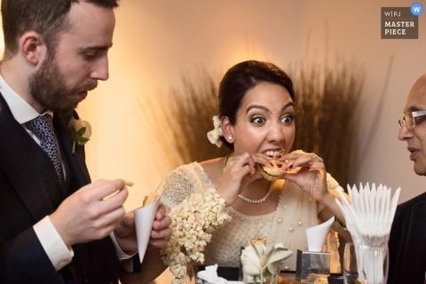Der Londoner Hochzeitsfotograf hat dieses Foto der Braut aufgenommen, die beim Hochzeitsempfang einen Aperitif genießt