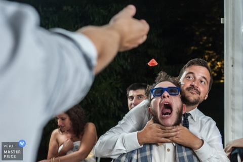 Venice wedding photographer shoots the action of the groomsmen playing games with their food at the reception