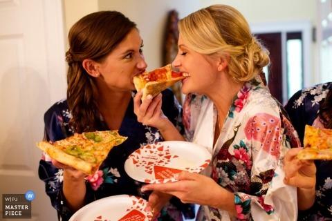 Vorsehungshochzeitsfotograf fing die Braut und die Brautjungfern, die ein Stück Pizza vor der Zeremonie genossen