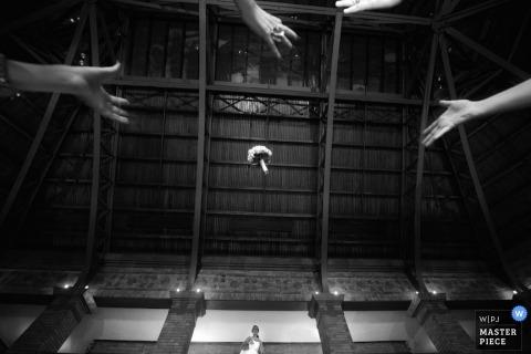 Fotograf ślubny z Chicago wykonał to czarno-białe zdjęcie przedstawiające gości weselnych, które sięgają ponad aparat, by złapać bukiet