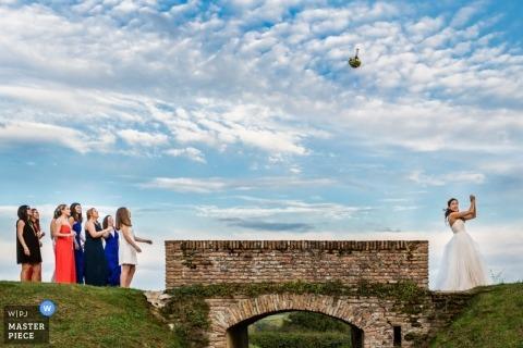 Trouwfotograaf uit Montpellier maakte deze foto van een bruid die haar boeket onder een blauwe lucht gooit terwijl bruiloftsgasten aan de andere kant van een brug wachten om het te vangen