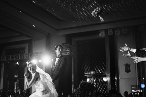 This black and white photo of the bride tossing her bouquet at the reception was captured by a Shanxi wedding photographer