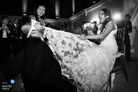 Montreal wedding photographer seized the moment in this black and white photo of the groom removing the garter with his teeth from the brides leg