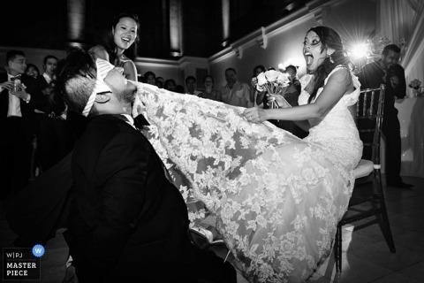 Montreal-Hochzeitsfotograf nutzte den Moment in diesem Schwarzweiss-Foto des Bräutigams, der das Strumpfband mit seinen Zähnen vom Brautbein entfernt