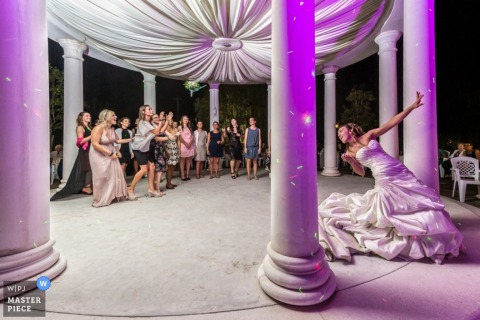 Venice wedding photographer freezes the action in this image of the bride throwing the bouquet at the reception under purple lights