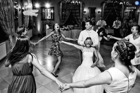 The guests dance in a circle around the bride while the groom covers her eyes in this black and white award-winning wedding image composed by a Krakow, Malopolskie photographer.