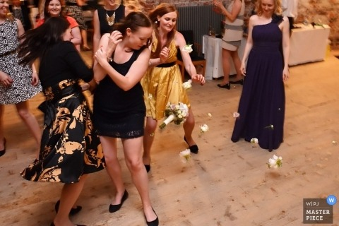 Helsinki wedding photographer captured this photo of some wedding guests running towards and other guests dodging the tossed bouquet during the wedding reception