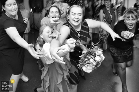 Helsinki wedding photographer shoots the action of the wedding guests leaping for the bridal bouquet in this black and white photo