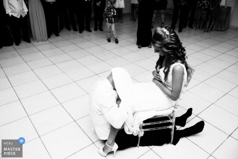 Puerto Rican wedding photographer caught the action of the groom removing the brides garter in this black and white image