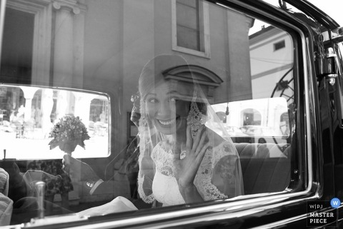 Brescia wedding photographer gets a black and white shot of the bride waving goodbye out of the car window as they drive away from the ceremony