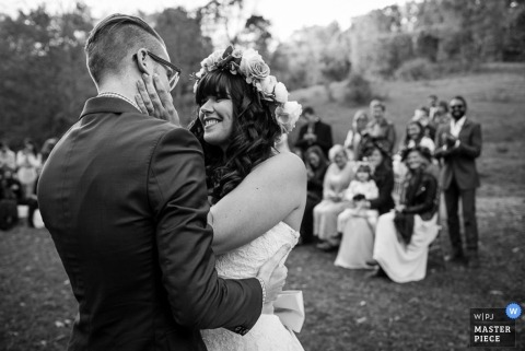 Denver wedding photographer caught the moment of the bride wearing a floral crown smiling at the groom in this black and white photo of an outdoor wedding ceremony