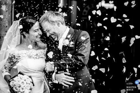 De trouwfotograaf van Lecco maakt een zwart-wit beeld van de bruid en bruidegom die na de ceremonie worden overladen met confetti