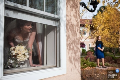 Montana wedding photographer makes a picture of the bride looking out the window while waiting for the ceremony to start