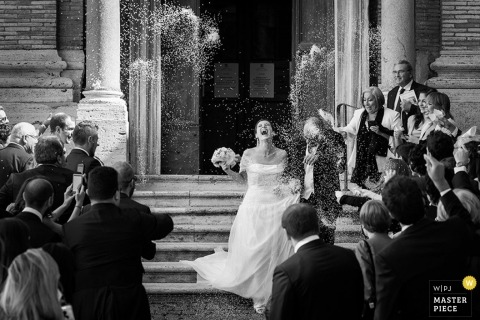 Rom-Hochzeitsfotograf fing den Moment in diesem Schwarzweiss-Foto der Braut und des Bräutigams ein, die die Kirche verlassen und im Reis geduscht werden
