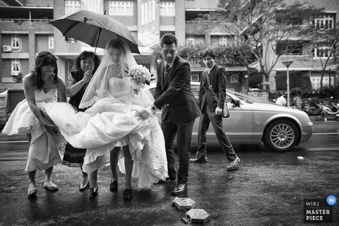 A bride gets assistance with holding her dress up as she and other wedding guests make their way through a rain storm in this black and white image created by a Taipei wedding photographer