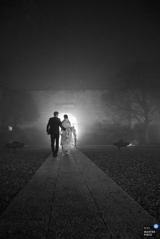 Brescia wedding photographer seized the moment of the bride and groom walking down the path in the dark   in this beautiful black and white image