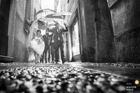 Arezzo wedding photographer freezes the action in this image of the bride and groom running down an alley in the pouring rain
