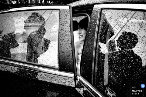 Montreal wedding photographer captured this black and white image of a bride sitting in a rain covered car getting ready to walk into the ceremony