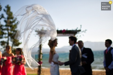 Lake Tahoe wedding photographer seized the moment in this photo of the brides veil being whipped around by the breeze from the lake
