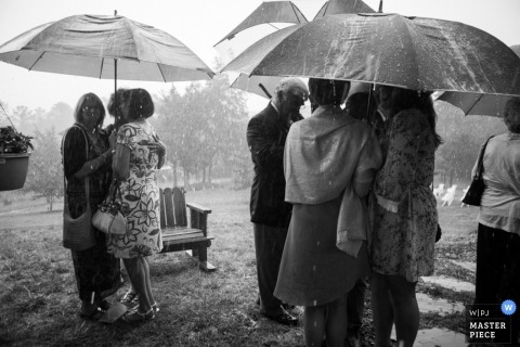 Raleigh wedding photographer created this black and white photo of the wedding guests huddling under umbrellas during a rain storm