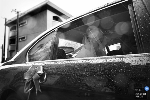 A rainstorm doesn't stop the bride from looking regal in this black and white image created by a Tainan wedding photographer