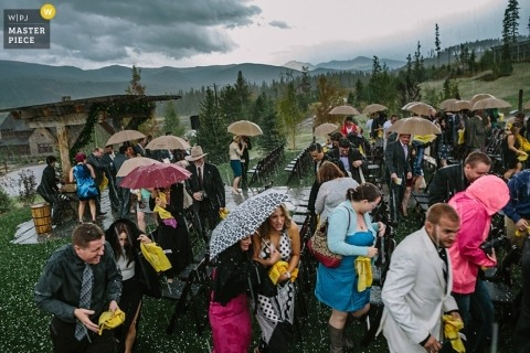 New Haven wedding photographer makes an image of the wedding guests sheltering under umbrellas at an outdoor ceremony