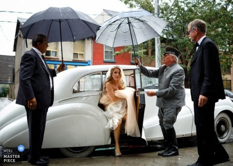 Toronto wedding photographer creates a picture of the bride being helped out of a classic car while being sheltered with umbrellas held by wedding guests