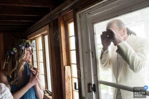 Portland wedding photographer captured this image of the bridesmaids getting ready in a cabin while the groom tries to sneak a peak
