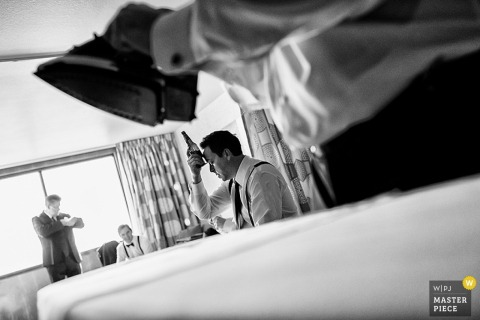 Lake Tahoe wedding photographer makes a black and white image of the groom chilling his head with his beer before the ceremony