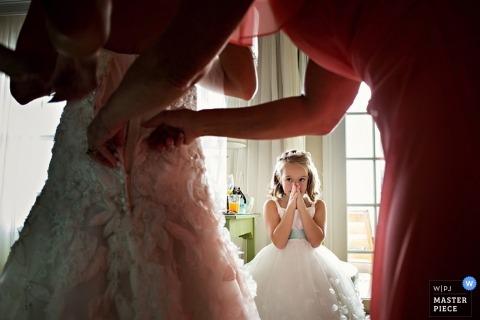 Key West-huwelijksfotograaf maakt een foto van een klein meisjes verrast gezicht aangezien zij let op de huwelijkstoga die op de bruid wordt geregen