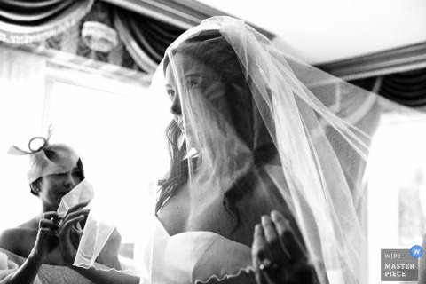 Rome wedding photographer makes a black and white picture of the bride putting on her veil before the ceremony