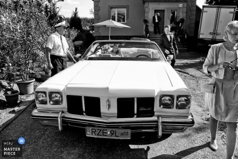 Krakow wedding photographer captured this black and white photo of the bride sitting in a classic convertible