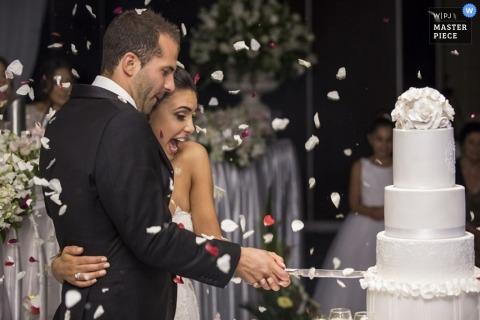 Sydney wedding photographer captured this joyful photo of a bride and groom cutting their cake as confetti falls around them