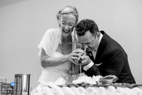 Le photographe de mariage de Munich fige l'action dans cette image en noir et blanc de la mariée et du marié coupant le gâteau à la réception