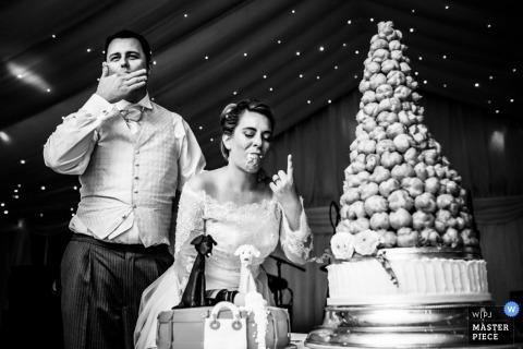 De trouwfotograaf van Devon heeft deze zwart-witfoto gemaakt van de bruidegom die zijn vingers likt na het breken van cake in het gezicht van de bruid