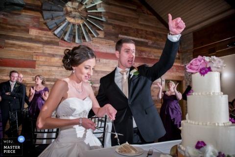 El fotógrafo de bodas de Chicago creó esta foto de la novia y el novio cortando su pastel de bodas en su recepción rústica.
