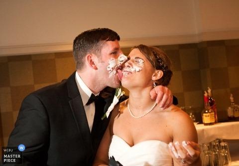 Fotograf ślubny Omaha zawiesza akcję na tym zdjęciu twarzy młodej pary młodej pokrytej ciastem