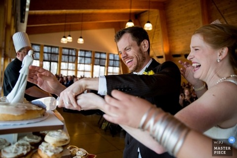 Chicago wedding photographer freezes the action in this image of the bride and groom cutting the cake at the reception