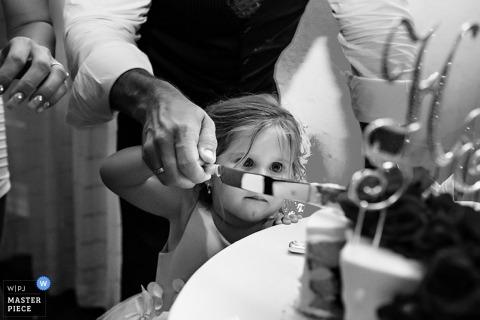 Deze foto van een klein meisje dat zorgvuldig helpt om de cake te snijden werd gecreeerd door een het huwelijksfotograaf van Key West