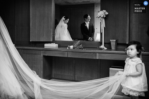 Hangzhou City wedding photographer created this black and white photo of a toddler holding the brides train as we see her reflection in the mirror behind
