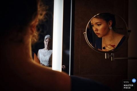 Un photographe de mariage montréalais crée une image des reflets de la mariée et des demoiselles d'honneur se préparant pour la cérémonie