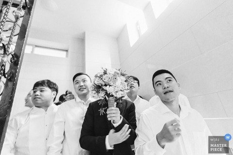 The groom's face is blocked by a bouquet of flowers as he stands with his groomsmen in this black and white photo by a Fujian, China wedding photographer.