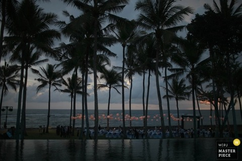 Bali wedding photographer created this distance shot of the wedding reception taking place below the palms at dusk