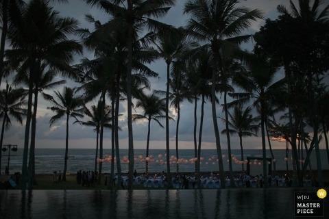 De trouwfotograaf op Bali maakte deze afstandsfoto van de bruiloftsreceptie onder de palmen in de schemering