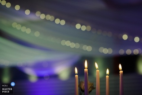 Baden-Wurttemberg wedding photographer created this detail image of five candlesticks burning in front of a canopy lit up with purple and green lights