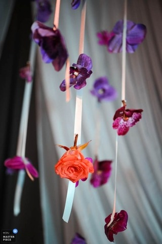 Chicago wedding photographer photographed the purple and pink flowers hanging from the ceiling at the reception