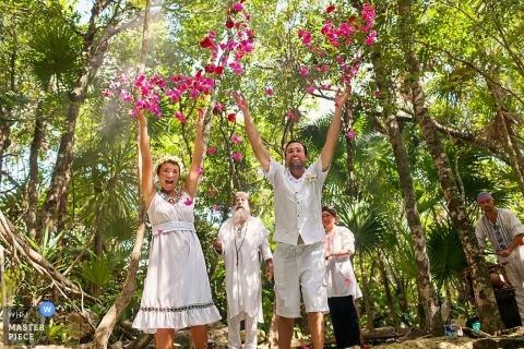 Playa del Carmen trouwfotograaf bevriest de actie in dit beeld van de bruid en bruidegom die rozenblaadjes in de lucht gooien tijdens hun tropische buitenceremonie