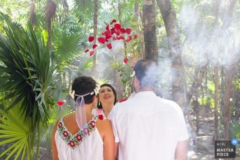 De trouwfotograaf van Playa del Carmen greep het moment vast op deze foto van de rozenblaadjes die op de bruid en bruidegom vallen terwijl ze hun ceremonie houden in een tropisch bos