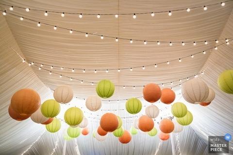 Un photographe de mariage du New Jersey a capturé ce détail de lanternes en papier vert, pêche et blanc suspendues sous une tente blanche