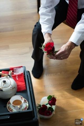Alberta-Hochzeitsfotograf macht ein Bild des Bräutigams, der einen Boutineer beim Genießen einer Tasse Tee hält